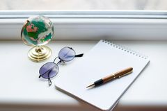 Notebook opened on white desk with pen, globe and black glasses. View from above royalty free stock images