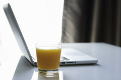 Notebook Orange Juice. Notebook with glass of orange juice on the white table under window natural lighting Royalty Free Stock Photos