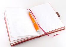Notebook and orange pen Royalty Free Stock Photography