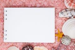 Notebook over pink bath salt and seashells Royalty Free Stock Photos