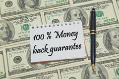 Notebook page with text 100% MONEY BACK GUARANTEE on dollar background. Closeup stock photos