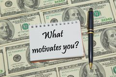 Notebook page with text WHAT MOTIVATES YOU on dollar background Stock Photos