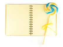 Notebook with pale lined paper and lollypop. Isolated on white background Stock Image