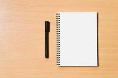 Notebook paper with blank page for copyspace and blakc pen for n. Ote message on wooden table stock photos