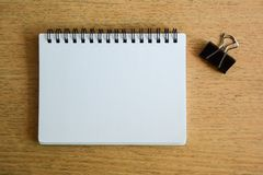 Notebook and paper clip on wood desk Stock Photography