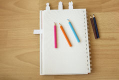 Notebook paper and color pencils. On wood background Stock Photography
