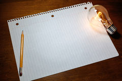 Notebook paper and light bulb Stock Photography