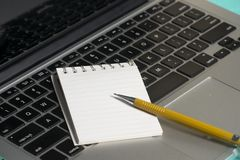 Notebook and a paper note. A notebook, paper note and a mechanic pen laptop background computer business technology digital design notepad work communication stock images