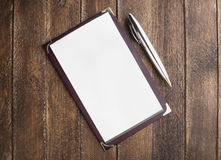 Notebook paper with pen on wooden table Stock Images