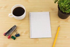 Notebook paper with pencils, coffee, thyme on flowerpot, stapler and paperclip on brown wood table background Royalty Free Stock Photo