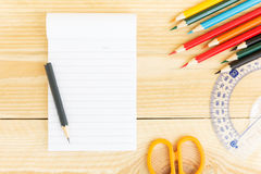 Notebook paper and school or office tools on wood table Stock Images