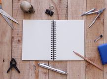 Notebook paper and tools on wood background Stock Photos