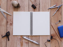 Notebook paper and tools on wood background Royalty Free Stock Photos