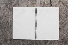 Notebook paper on wood background Royalty Free Stock Photography