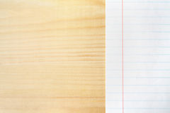Notebook paper on a wooden table. Lined paper background with free text space. Stock Image