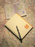 Notebook and passport on a map Stock Image