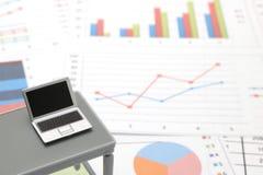 Notebook PC e documenti di affari con i numeri ed i grafici Immagini Stock Libere da Diritti