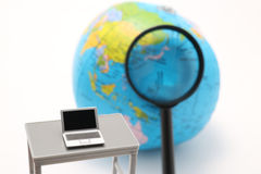Notebook PC, magnifying glass and globe on white background. Royalty Free Stock Photography