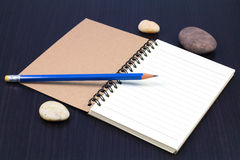 Notebook, Pebble Beach and blue pencil Royalty Free Stock Photos