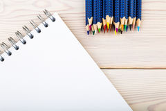 Notebook and pecils on wooden desk Royalty Free Stock Image