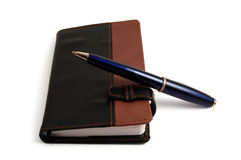 Notebook and pen. Black notebook and blue pen Royalty Free Stock Photo