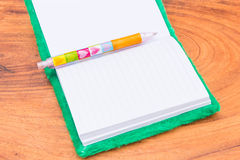 Notebook and Pen. Velvet Notebook and Pen on wood background Royalty Free Stock Image