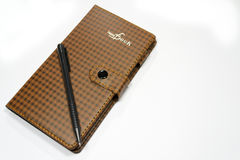 Notebook with pen. Brown notebook with pen, isolated in white background Royalty Free Stock Image