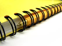 Notebook with pen. Yellow spiral ring bound notebook with ballpoint pen inside the spiral stock image