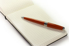 Notebook and pen. A luxury red pen on a notebook Royalty Free Stock Photos