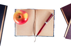 Notebook with pen and apple. Opened notebook with pen and apple isolated Royalty Free Stock Photo