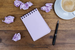 Notebook with pen aside coffee crumpled paper on wooden table Royalty Free Stock Image