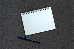 Notebook and pen on asphalt texture Royalty Free Stock Photos