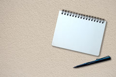 Notebook and pen on beige plaster texture Stock Image