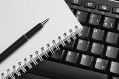 Notebook and pen on the black keyboard. Stock Photos
