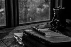 Notebook with pen. A black and white closeup of a notebook with a pen on a wooden table Royalty Free Stock Image