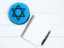 Notebook, pen and blue kipa on a white wooden background, top view. Jewish New Year, Rosh Hashanah Royalty Free Stock Images