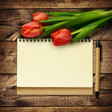 Notebook and pen with bouquet of tulip flowers Stock Photo