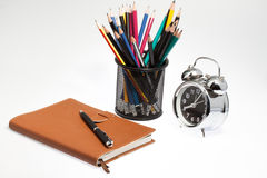 Notebook with pen box and clock Royalty Free Stock Photos