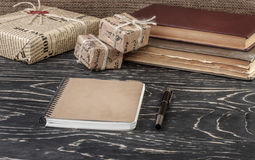 Notebook pen and a box of old books on a wooden table Royalty Free Stock Image