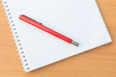 Notebook and pen. On brown table Royalty Free Stock Photo