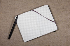 Notebook with pen on burlap Royalty Free Stock Photos