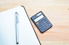Notebook and pen with calculator on wooden table Royalty Free Stock Photos