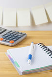 Notebook with pen, calculator are on a wooden table. On the wall near the table glued paper for notes. Stock Photography