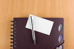 Notebook, pen and card. Notebook with metal pen and blank card on wooden table Royalty Free Stock Images