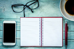 Notebook,pen,cellphone, glasses and coffee on wooden table Stock Images