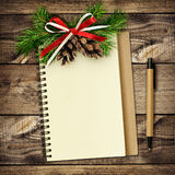 Notebook and pen with Christmas decorations on wood Royalty Free Stock Photo
