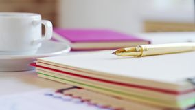 Notebook, pen, coffee cup and other accessories on the desk. Workplace of a businessman.
