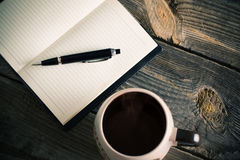 Notebook with pen and coffee on  wooden table Royalty Free Stock Photo