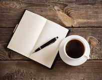 Notebook with pen and coffee on wooden table Stock Photos