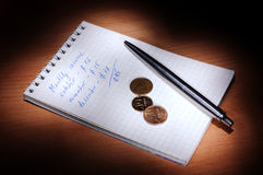 Notebook with pen and coins in the dark Stock Image